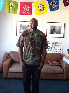 A picture of Taylor Code standing in front of a brown couch with a wall in the background that has two black and white framed pictures and turquoise, green, yellow, navy blue, and purple flags hanging from ceiling over his head.