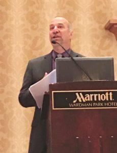David Lee, bading white man in black jacket and purple shirt, standing behind podium