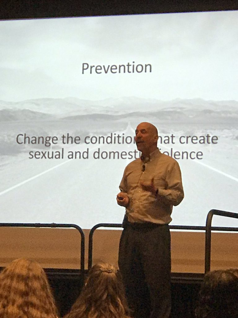 """David Lee (balding white man in white shire and dark pants) standing in from on screen saying """"Prevention: Change the conditions that create sexual and domestic violence"""""""