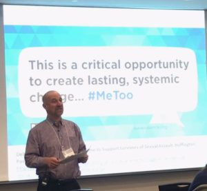 "David Lee, a baolding white man stading in front of screen saying ""This is a critical opportuhnity to lasting systematic change... #MeToo"""