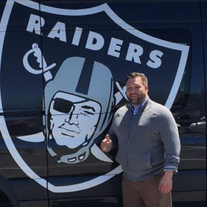 White man with beard and gray sweater staniding in front of Oakland Raiders logo.