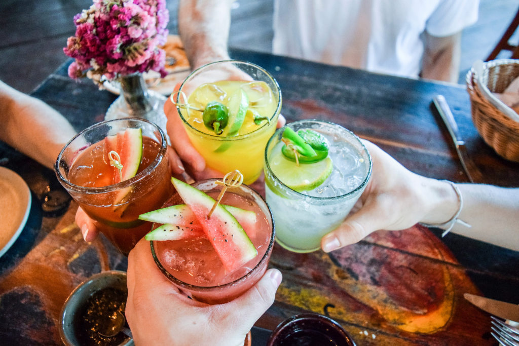 Friends toasting, saying cheers holding tropical blended fruit margaritas. Watermelon and passionfruit drinks.; Shutterstock ID 780298633; AP/Pedido de Compra (opcional): -