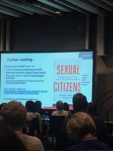 """A projection screen with a PowerPoint slide showing the cover of an upcoming book. The book has a white cover with the words """"Sexual Citizens"""" in red font."""