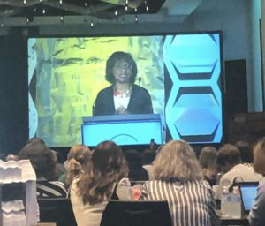 A photo of Dr. Anita Hill on a projection screen. Dr. Hill is behind a podium.