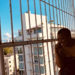 a black women on a railed balcony smiling and looking down below the balcony