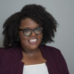 a smiling black woman wearing glasses and a purple blazer on a grey background