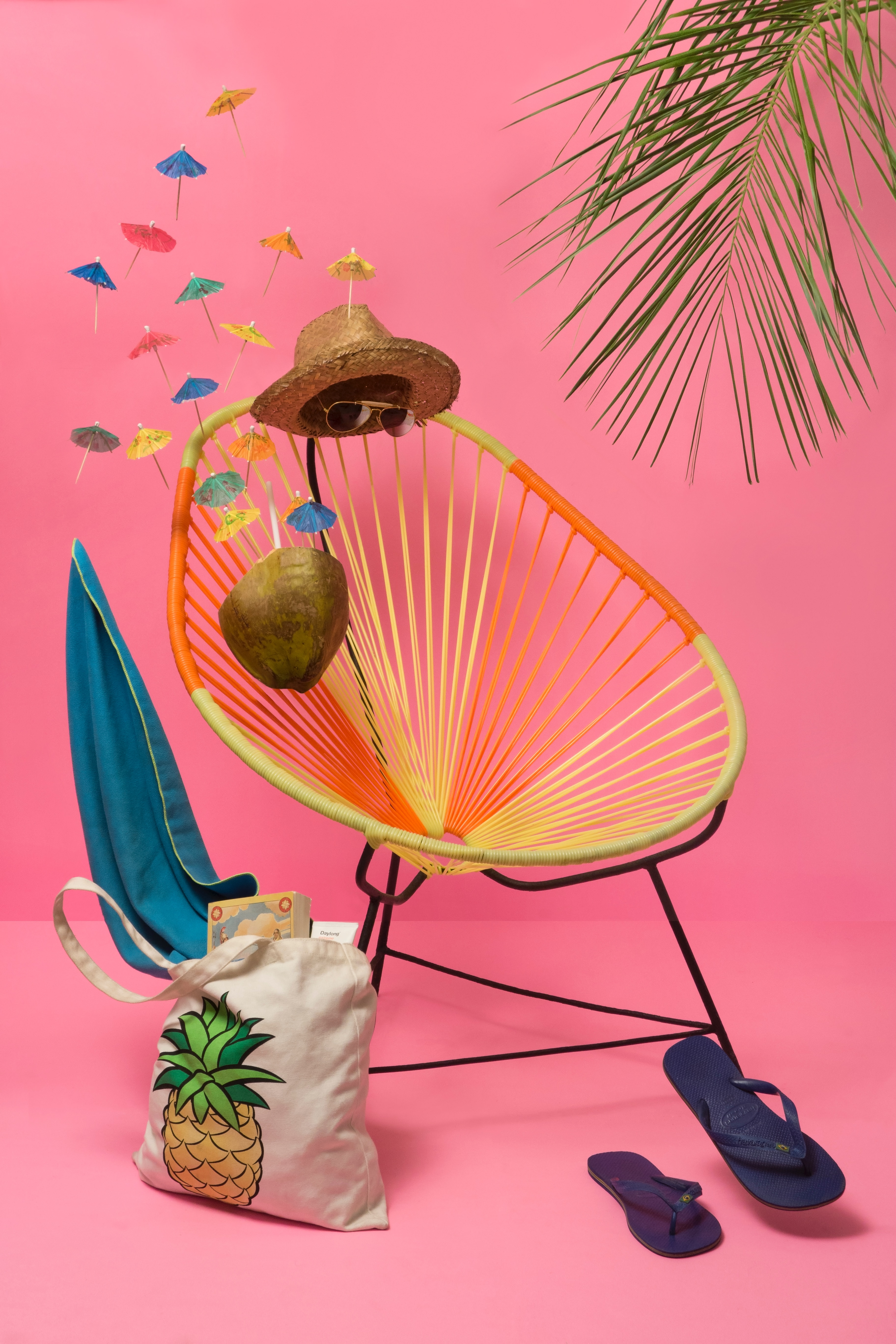 Photo of a circular lounge chair with floating sunglasses, a hate, a coconut drink, and flip flops like an invisible person is sitting in the chair