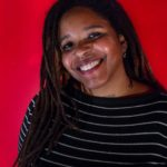 Image of Aisha Shillingford. A black woman with locs and a nose ring smiles into the camera. She's wearing a black shirt with white stripes and is in front of a red background