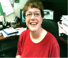 picture of Gail Burns Smith sitting in a red blouse