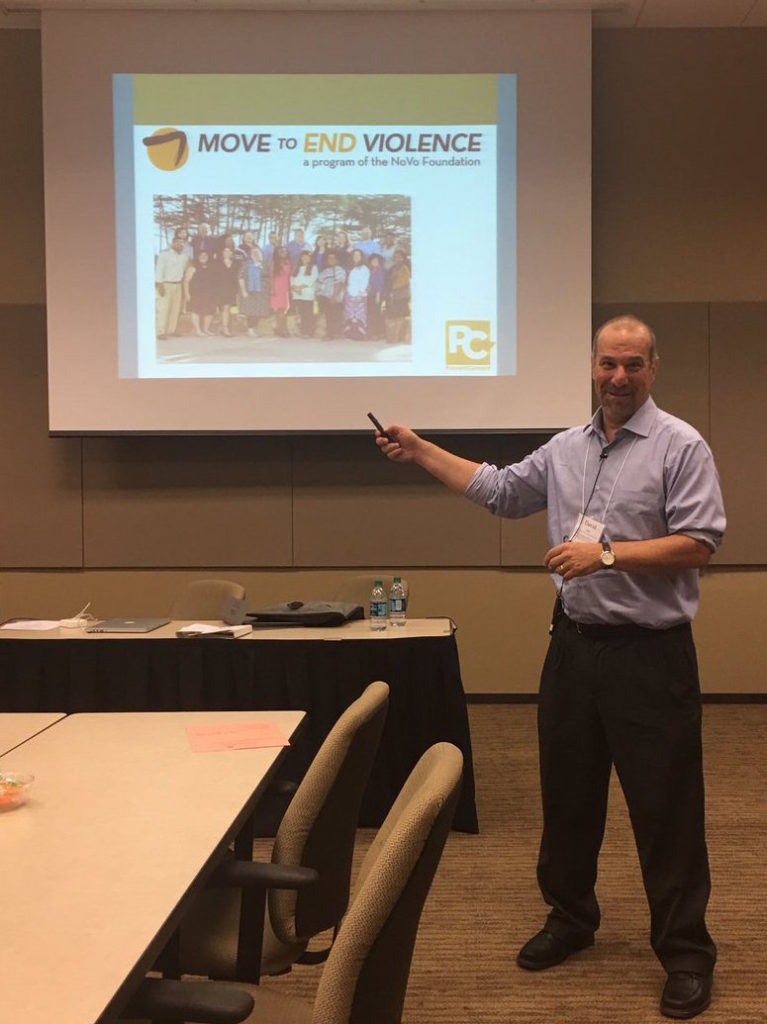 David Lee, bearded white man with short hari pointing at a screen showing Move to End Violence