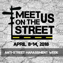 """""""Meet Us on the Street"""" written in black letters with an illustration of a street and street signs framing the words. The dates April 8-14, 2018 and the words """"Anti-Street Harassment Week"""" are below"""