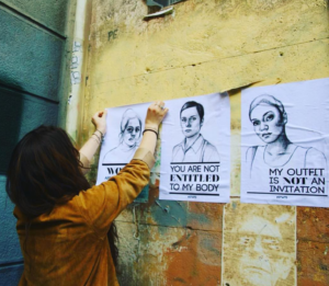 """Women pasting up 3 """"Stop Telling Women to Smile"""" posters. The center and the right poster have visible text. Center: black and white sketch of a women with short hair with the text """"You are not entitled to my body."""" Right: black and white sketch of another woman with short hair with text """"My outfit is not an invitation."""" For more information about International Anti-Street Harassment Week, go to http://www.meetusonthestreet.org/"""
