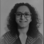 Black and white photo of a women with glasses and curly hair smiling