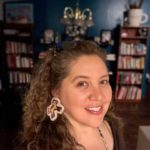 picture of a woman with brown curly hair smiling with a bookcase full of books behind her