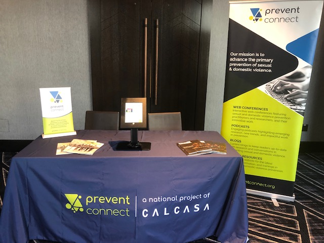 A photo of PreventConnect's informational table. The rectangular table has a dark blue tablecloth with the PreventConnect logo in green. A floor banner is located to the right of the table and a tabletop table is on the right side. There are written materials on the table and an iPad stand in the center of the table.