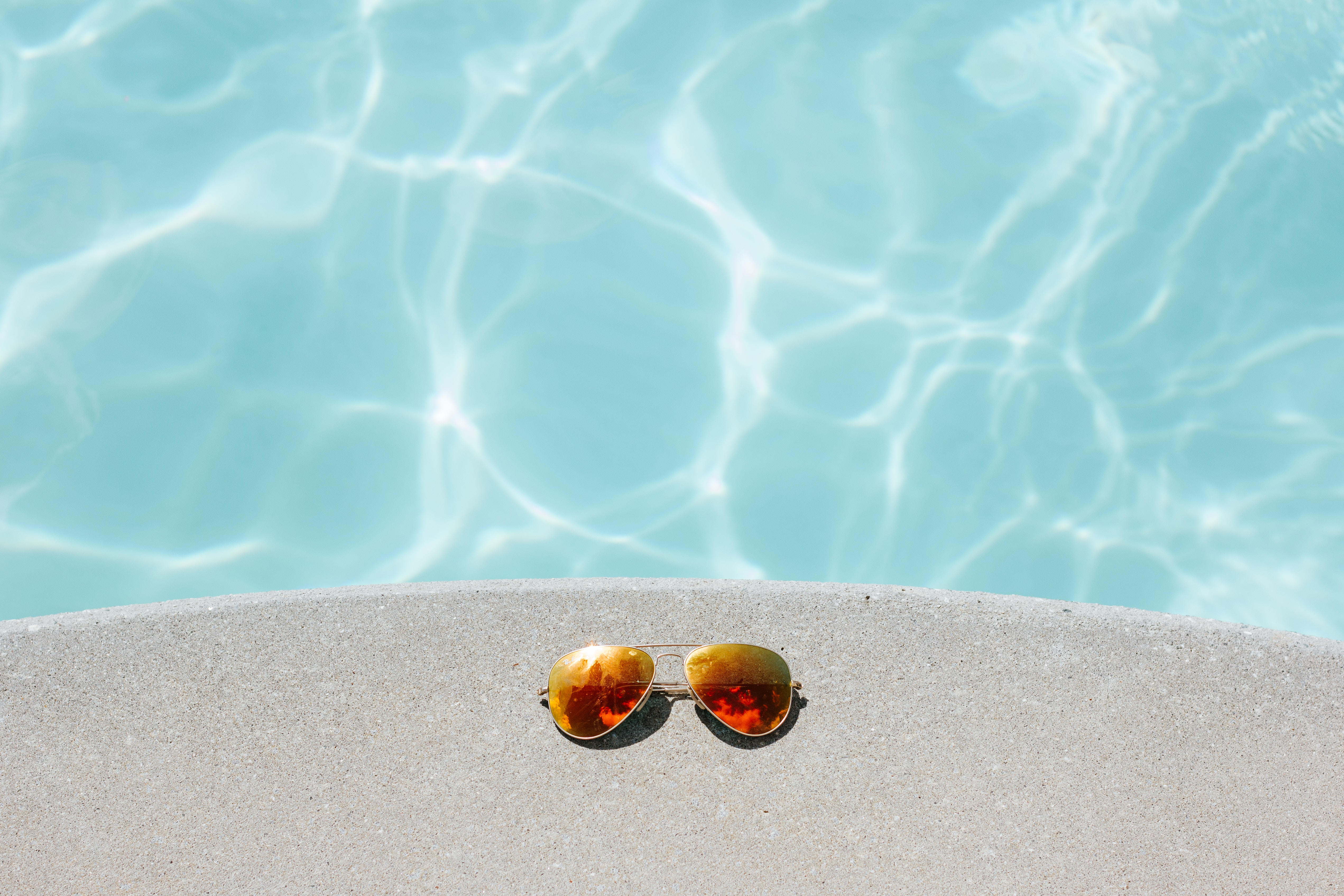Image of sunglasses sitting on the ledge by the pool