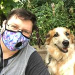 Image description: Skye, a young, disabled, white trans person, sits outside with one of their pups, Cricket, an orange and creme shepherd mix. Skye is wearing thin-rimmed rectangular eye glasses, small white headphones, a gray Henley shirt, and a blue, white, and pink swirly-styled (trans pride colours!) breathing mask. Cricket and Skye are both smiling and behind them is a mess of tall green plants.