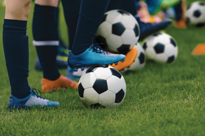 Below the knee image of multiple soccer players wearing cleats balancing and standing on a soccer ball