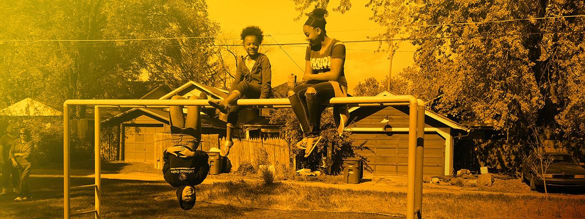 three youth on a playground gym